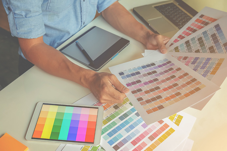 architect drawing: Graphic design and color swatches and pens on a desk. Architectural drawing with work tools and accessories.