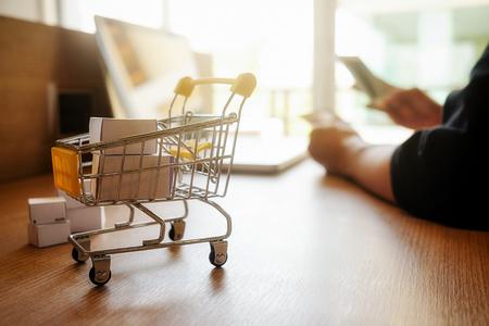 Internet concepto de compras en línea con el portátil y carrito de compras.Vintage efecto de filtro retro tono, enfoque suave (enfoque selectivo) Foto de archivo