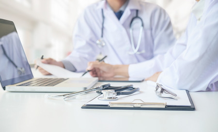 Stethoscope with clipboard and Laptop on desk,Doctor working in hospital writing a prescription, Healthcare and medical concept,test results in background,vintage color,selective focus Archivio Fotografico