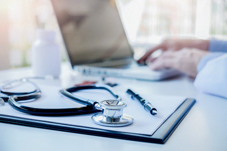 Stethoscope with clipboard and Laptop on desk Doctor working in hospital writing a prescription  Healthcare and medical concept test results in background vintage color selective focus. Stockfoto