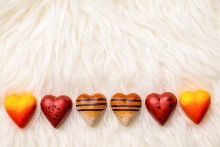 shaped: Valentine theme: Heart-shaped chocolate on fur texture.