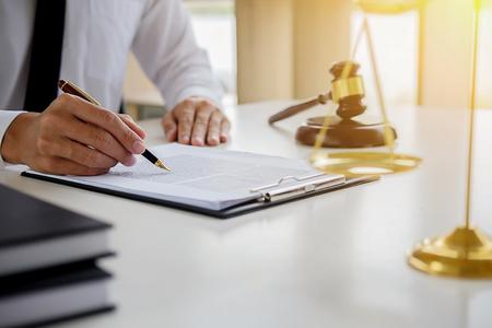 Justitie en recht concept. Juridisch adviseur presenteert aan de cliënt een ondertekend contract met hamer en juridische of juridische teamvergadering bij advocatenkantoor op de achtergrond