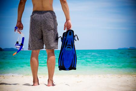 Happy man relaxing enjoying on the beach with snorkeling gear. Summer beach vacation. 版權商用圖片