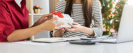 Business woman manager giving a present to her colleagues in last working day. Young creative people are celebrating holiday in modern office. Merry Christmas and Happy New Year.
