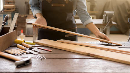 Carpenter working with equipment on wooden table in carpentry shop. woman works in a carpentry shop. Archivio Fotografico