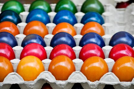 egg carton: Colorfully dyed eggs-red, yellow, blue, green, orange, purple-in an egg carton Stock Photo