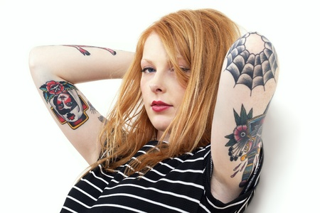 Strawberry blonde with tattooed arms leaning against a white wall wearing red lipstick and a striped top photo