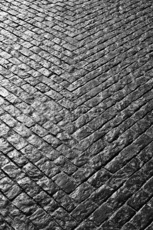 evocative: Grey cobbled street with bricks making a V shape Stock Photo