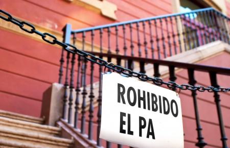 no pase: Una señal en parte la lectura no pasan en español, dando lugar a un conjunto de escaleras en el lado de un edificio rojo