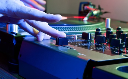 crossfader: Hand of a DJ pushes the crossfader of a mixing desk in a colourful club environment Stock Photo
