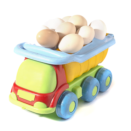 chicken eggs on toy car on white background with blank card. Abstract retro concept.