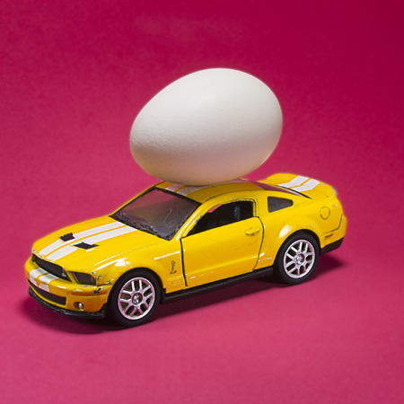chicken eggs on toy car on red background with blank card. Abstract retro concept.