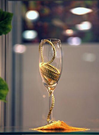 goldish: decorative tall wine glass with a goldish rope  on a window