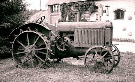 agriculture machinery:  old tractor with iron wheels is thrown on a roadside Stock Photo