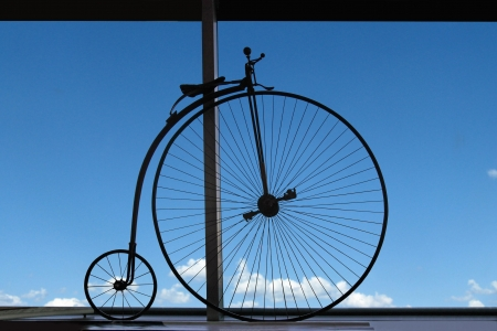 Old bicycle on a window sill against the blue sky photo