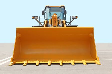 The orange bulldozer on a concrete platform against the sky photo