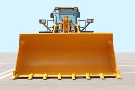 The orange bulldozer on a concrete platform against the sky photo