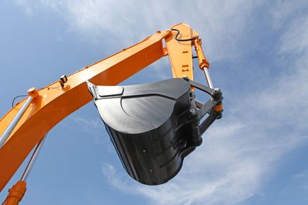 trencher: Orange clear excavator bucket against the blue sky