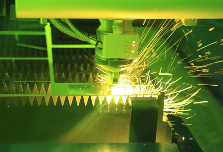 Industrial laser cutter with green background, with sparks  Stock Photo