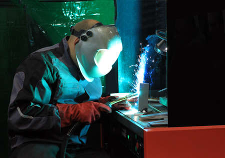 Welder uses torch to make sparks during manufacture of metal equipment. Stock Photo - 9964879