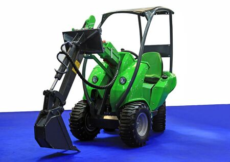 green modern little excavator machines on a dark blue carpet Stock Photo - 10389149