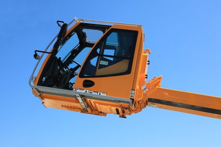 maneuverable: Operated cabin of the elevating crane against the sky