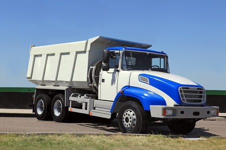Heavy dump-body truck with the big body on the road