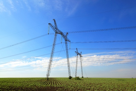 high powered: Electric power lines on the field against the blue sky
