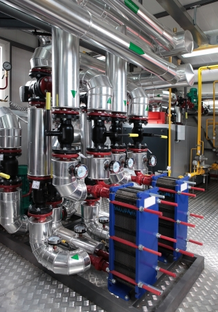 Interior of independent modern gas boiler room with manometers, valves, pumps and thermo-insulation on pipelines