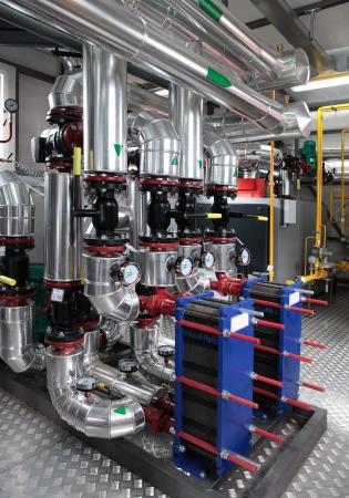 Wnętrze niezależnych nowoczesnych kotłowni gazowych z manometrów, zaworów, pomp i termo-izolacji na rurociągach