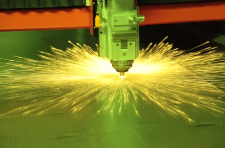 Laser cutting metal sheet in factory, with sparks flying around  photo