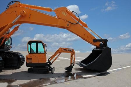 backhoe: Two excavators on a concrete platform  Big and small excavators for comparison by a row