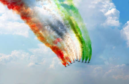 on cloud nine: The group of nine planes draws color smoke strips in the sky