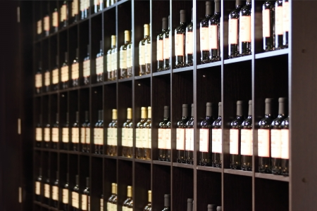 Rack with bottles of different wine in shop of elite wines