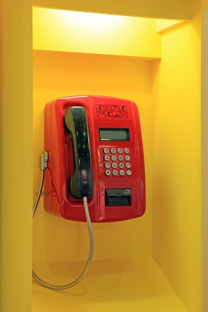 Red public telephone in the yellow booth with lighting photo