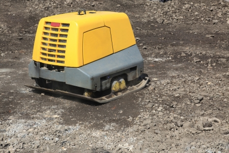 vibrating: Vibrating compactor soil with remote control via radio Stock Photo