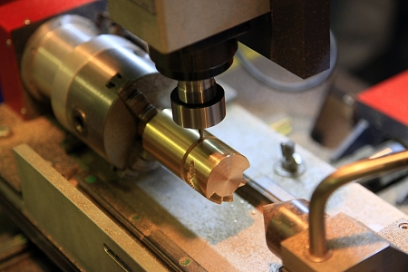 Milling machine handles the detail of brass complex shape Stock Photo