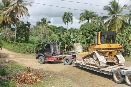 bad banana: truck transports bulldozer in the jungle on a bad road