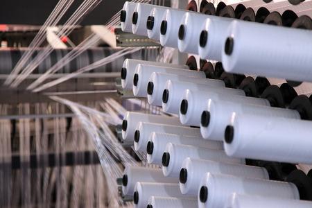 grote groep van onderdraad kegels op een kromtrekken machine in een textielfabriek Stockfoto