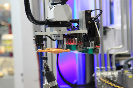 Industrial robot moves ready screwdriver in the machine