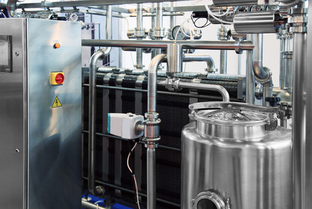 Dairy factory with milk pasteurization tank and pipes  Stock Photo