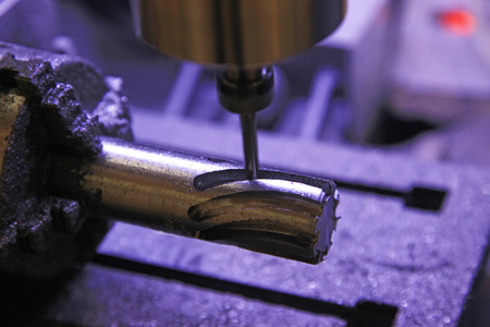 CNC milling machine handle grooves in a cylindrical workpiece photo