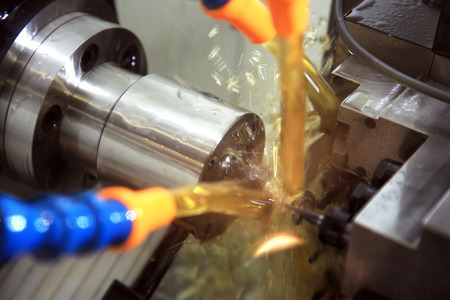 metal processing: metal blank machining process on lathe with cutting tool and coolant at steel manufacturing