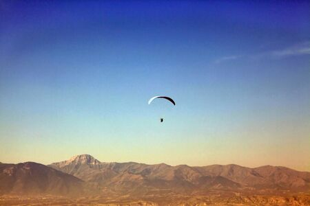 paraglide: Paraglide silhouette flying over mountains in Denizli, Turkey Stock Photo