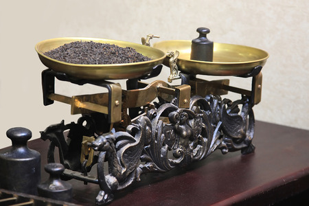 counterbalance: Old-fashioned balance scale with black tea