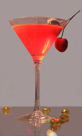 aperitive: the cocktail glass with cherry on a gray background Stock Photo