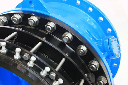 The flanges of valves with bolts and nuts. Connecting fittings of different diameters. Stock Photo