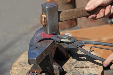 ferreteria: La forja billete de acero en el yunque con un martillo Foto de archivo