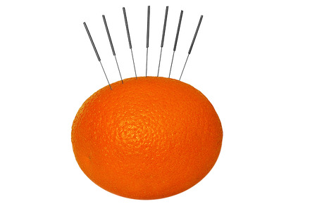 needless: Orange used to demonstrate the use of Acupuncture needless  Stock Photo