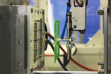 La máquina de moldeo por inyección expulsa la pieza terminada.